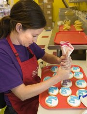 Sara Tramp puts icing on small sugar cookies for a special order.