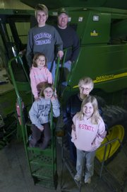 The Wulfkuhle family won the first water quality award given by the Douglas County Conservation District. Standing on the big combine machine are Mark and Brenna Wulfkuhle with their three daughters, Baylee, Madison and Kelsey, along with Judy Wulfkuhle.
