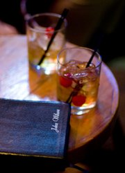 The Bible of John Wilson sits readily at hand next to a couple of drinks at Henry's, 11 E. Eighth St.