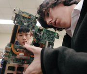 Bishop Seabury Academy seniors Steven Peng, left, and Jefferson Wagner, right, inspect a laptop computer circuit board in class.