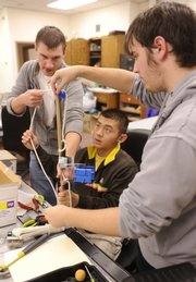 Lawrence High School engineering students, from left, Austin Strout, Vienney Phiomavong and Tyler Parker practice for the Construction Challenge competition, which will be this weekend in Kansas City. The students gathered Thursday at the school, 1901 La.