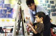 Preschooler Joel Cisneros, 4, works on an art project as his teacher, Ann Johnson, assists at the Lawrence Arts Center.