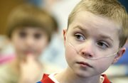 Wellsville elementary school fifth-grader Michael Douglas listens during class. Michael is an honor roll student despite a rare lung disease that has kept him out of school for weeks here and there since kindergarten.