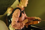 Tricia Spencer, a member of The Prairie Acre, tunes her instrument with her 1-year-old daughter Ruby Yother strapped to her back.