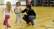 New York school principal Nancy DeGarmo visits with Monica Thibeaux, a kindergarten student in the gym. DeGarmo began her professional career after her three sons started school.