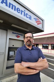 Recently unemployed engineer Arthur Santa-Maria stands in front of a Bank of America ATM in Los Lunas, N.M. Santa-Maria was surprised to learn he must pay fees to withdraw his unemployment money using a state-issued bank debit card.