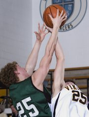 Senior Chase Hoag (left) fights for the ball with Viking junior Matt Kieffer. Free State boys lost to Shawnee Mission West Friday 50-54.