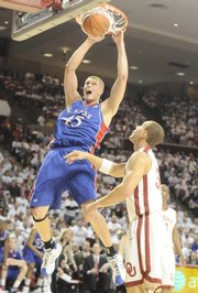 Kansas center Cole Aldrich delivers a dunk on Oklahoma forward Taylor Griffin during the second half at the Lloyd Noble Center in Norman, Okla.