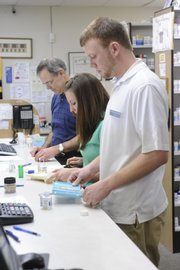 Pharmacist Mark Smith, left, and interns Katherine Ward and Mike Hrenichir fill prescriptions on Wednesday at Orchards Drug, 1410 Kasold St. A genetic drug company called Ethex, which was available at Orchards Drug, has recently been pulled from the shelves.