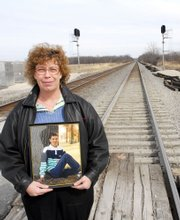 "Janet Harris holds a picture of her late stepson, Eric Harris, at the railroad crossing where his vehicle was struck by a train in September 1998. ""It took me about a year before I was able to cross any railroad tracks,"" Harris said. Crossing arms and lights have been installed at the crossing since the accident."