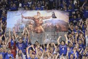 The Jayhawk student section displays an enlarged and modified version of artist John Steuart Curry&#39;s &quot;Tragic Prelude&quot; painting, which features abolitionist John Brown holding a rifle, and in this case the 2008 National Championship trophy.