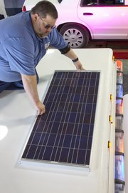 Terry Eaton installs a new solar panel Wednesday on a Lawrence city ambulance. The solar panel will allow the ambulance's electronic systems to receive power without the engine running, reducing fuel consumption and emissions.