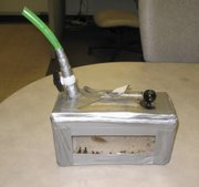 Homemade bong, consisting of a piece of garden hose attached to a duct-taped plexiglas box.