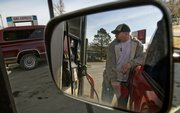 Jason Smith fills up his car with gasoline at Woody's Gas Express in North Lawrence. Gasoline prices are expected to climb this summer but not to last year's record highs.