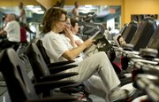 Lawrence resident Leslie Milton thumbs through a magazine while on a stationary bicycle at Lawrence Athletic Club, 3201 Mesa Way.