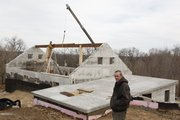 "Design-builder Kenton Knowles, foreground, oversees the construction of a ""green"" home near Oskaloosa for Tim O'Brien, who works on the roof beam above."
