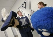 Xavier mascot Arick Stall, left, wearing the costume of D'Artagnan, talks with mascot Abby Strietmann, wearing the costume of the Blue Blob, prior to the game between Xavier and Dayton in Cincinnati.
