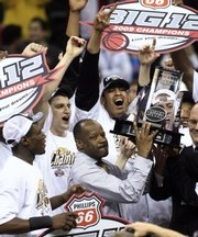 Missouri coach Mike Anderson holds up the Big 12 championship trophy after defeating Baylor 73-60 in the Big 12 Conference men's tournament championship game in Oklahoma City, Saturday, March 14, 2009.