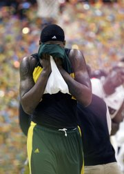 Baylor's Kevin Rogers covers his face as he leaves the court after the loss to MU.