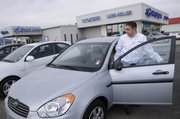 Steve Pickrell, Laird Noller Hyundai sales representative, checks out a car at the dealership, 2829 Iowa. Pickrell says the Hyundai car buyers insurance is the only one of its kind in the industry. Hyundai allows buyers to return their car without penalty if they get laid off from their job.