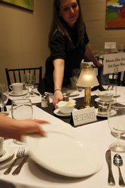 "Sandy Theilen sets a table with china at Maceli's Catering for a ""green wedding"" that will not use disposable place settings."