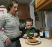 Eleana Walsh watches her son Carter make his peanut butter and jelly sandwich in Bow, N.H., in this Feb. 13, 2009, file photo. The peanut is a national icon — right up there with the hamburger and the apple, but the weeks-long salmonella scare has resulted in a pervasive suspicion of peanuts as a health hazard.