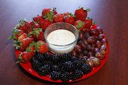 Fresh fruit and dip make a relatively healthy and inexpensive game snack. Save money on either fruit or veggie trays by slicing and washing produce yourself.