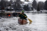 Lowell Bottrell paddles through the current in his neighborhood as the Red River continues to rise, Friday in Briarwood, N.D. Bottrell is one of the few left in his neighborhood.