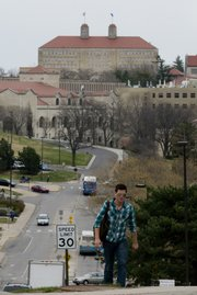 Kansas University sophomore Adam Vossen, of Tecumseh, makes his way to the top of the hill Wednesday at the intersection of 15th Street and Engel Road on campus. KU should renew its commitment to preserving historic portions of campus as the university grows, according to a campus heritage plan that was discussed at an event Wednesday.