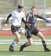Free State High's #7 Erin Ice works against Shawnee Mission West defender #13 Gina Kirkwood, Thusday April 2nd, at FSHS.