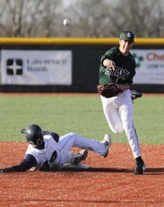 Free State senior second baseman Tyler Hatesohl throws to first base after forcing out Blue Valley North senior Mike Britton at second during the second inning Friday, April 3, 2009 at Free State High School.