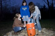 As the last light of day fades, Sidney Davis (from left), Laura Holt and Amber Remboldt fill the water container for their troop. Hidden Valley Girl Scout Camp celebrated the 50th anniversary of its cabin in 2009.