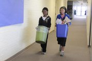 Broken Arrow School students Ahnya Lewis, 10, and Lexi Anglin, 10, carry blue recycle buckets to a sorting area. Sherry Emerson, with Lawrence PetSmart, which provided materials for the school, says many students are now recycling at home as well.