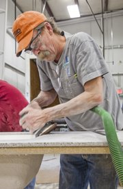 Cabinet maker Steve Tatum keeps busy by sanding a solid surface counter top at Tolar Cabinets even though work orders are down due to the recession.