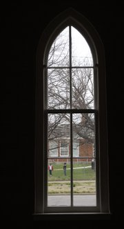 A view of children at recess at New York School is seen through one of four large windows in the living area at a renovated church site at 10th and New York streets.