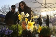 Kym Scafe, Lawrence, a worker with Pendleton's Country Market, retrieves a vase of daffodils for Lawrence resident Michael Rapport on the first day of the Farmer's Market Saturday, April 11, 2009.