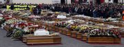 Coffins are lined up during the funerals for quake victims Friday in L'Aquila, central Italy. Four days after the major earthquake that made L'Aquila and many nearby towns and villages uninhabitable, the official death toll has reached 287, and most of the victims are here, in L'Aquilia.
