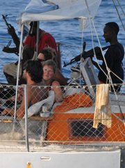 "In this undated photo released by the French Defense Ministry on Saturday, armed pirates and their hostages are seen aboard the French yacht ""Tanit"" off the coast of Somalia. The pirate scourge off the Somalian coast has greatly increased over the past year."
