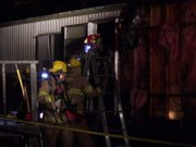 Firefighters inspect a mobile home that was damaged in a fire early Tuesday morning.