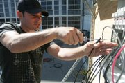 Duane Robinson installs wires during a class on solar panels recently at San Jose City College in California. Students and colleges are betting that President Barack Obama's campaign to promote alternative energy and combat global warming will create millions of green jobs that pay well, cannot be outsourced and do not require a four-year degree. See story, page 7B.