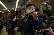 Late income tax filers make their way through the glass doors as members of the Alferd Packer Memorial String Band including Steve Mason, Lawrence, front, Jim Brothers, Lawrence, left, and Steve Goeke, Holt, Mo., perform the William Tell Overture during the final push before closing on Tax Night 2009 at the downtown Lawrence post office.