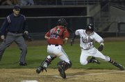 Catcher Jake Green waits at home for Joseph Ramriez who was called safe in the third inning. Lawrence lost to Bishop Ward 0-5 Friday in the River City Baseball Festival at the Community America Ballpark in Kansas City, Kan.