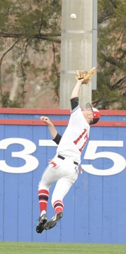 Lawrence High outfielder Tyler Bailey goes up to grab a fly ball in the 2nd inning Saturday April 18, 2009 against Blue Valley West.