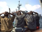 This file photo taken Jan. 4, 2009, originally provided by French Defense Ministry,  shows suspected pirates arrested by marine commandos of the French navy in the Gulf of Aden, off Somalia's coast. French government officials say the Jean de Vienne,background, intercepted and captured 19 pirates as they tried to take over two cargo ships.  Many captured Somali pirates once were freed because nations feared the complications of putting them on trial. But the world is now grappling with how to prosecute the bandits — and even considering a special tribunal.