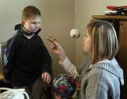 Danette Roth offers a toy Tuesday to her son, Lance Roth, 10, at their home in Parkville, Mo. Lance, born deaf and nearly blind, is now able to communicate better after taking part in a Kansas University study exploring communication methods for deaf-blind children.