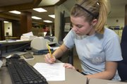 Rhianna Hoover, peer career assistant, edits a résumé that was e-mailed to the University Career Center at Kansas University. The UCC offers students help in navigating career paths and job applications.