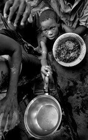 Clayson Menthor, 13, holds out a small pot for some beans and rice provided by a church outside of Cabaret, Haiti. This photo, taken Sept. 9, 2008, is one from a series that earned the 2009 Pulitzer Prize for Breaking News by Miami Herald photographer Patrick Farrell.