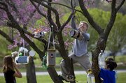 Deerfield fifth-grader Zachary Mayfield climbs up a tree to find a useable limb to hang his birdhouse Wednesday at the school, 101 Lawrence Ave. Diana Bailey's fifth-grade classes made birdhouses from recyclable materials in recognition of Earth Day. Along with Mayfield are his classmates Lucy McCleary, left, Tanner Hockenbury and in back and partially obscured is Samantha Travis.