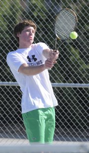 Free State's Michael Swank returns a shot to his Liberty, Mo., opponent. The Firebirds won the dual, 5-4, Wednesday at FSHS.