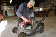 Paul Baumchen, Lawrence Parks and Recreation horticulturist, checks over a city lawn mower last week before heading out to mow in several city parks.